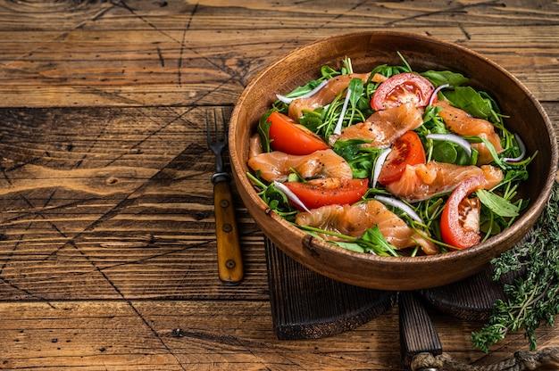 Salada de legumes com salmão defumado, rúcula, tomate e vegetais verdes. fundo de madeira. vista do topo. copie o espaço.