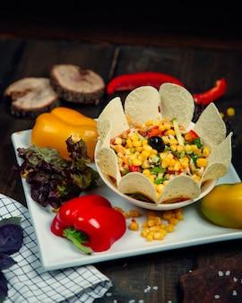 Salada de legumes com sementes de milho, pimentão de cor, ervas e batatas fritas.