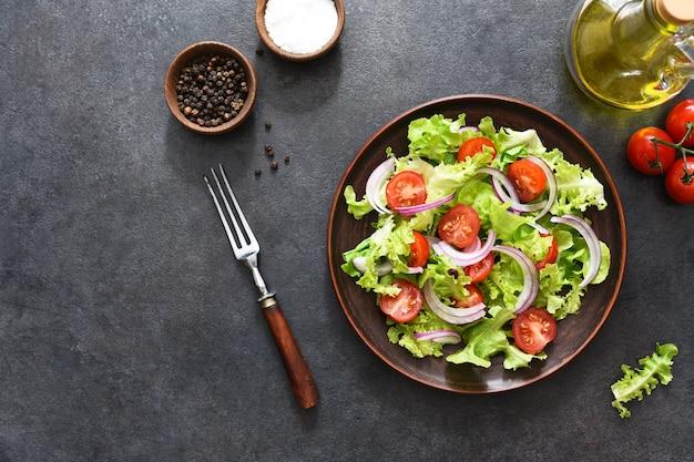 Salada de legumes com tomate, cebola roxa e molho preto, vista superior