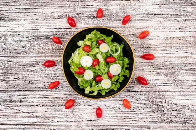 Salada de legumes com tomate cereja alface e cebola em uma tigela preta na superfície de madeira branca vista superior central