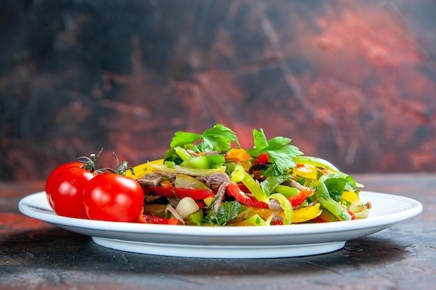 Salada de legumes com tomate cereja de vista frontal em prato oval em superfície vermelha escura isolada
