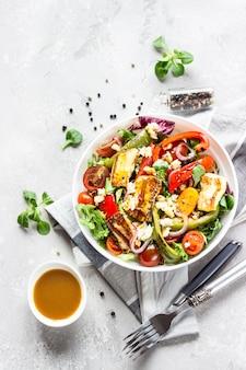 Salada de legumes com tomate cereja, pimenta assada, salada e cebola com queijo haloumi grelhado