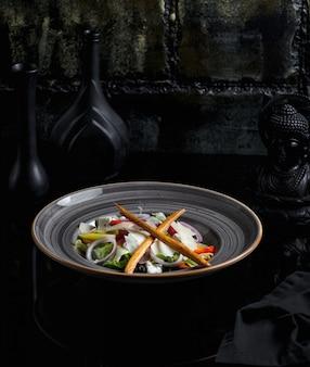 Salada de legumes contendo ingredientes misturados em um prato de cerâmica azul