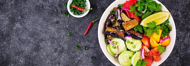Salada de legumes crus frescos - pepino armênio, tomate, pimentão, salsa, cebola roxa e berinjela cozida. tigela de buda vegan. bandeira. vista do topo