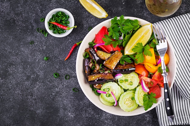 Salada de legumes crus frescos - pepino armênio, tomate, pimentão, salsa, cebola roxa e berinjela cozida. tigela de buda vegan. vista do topo