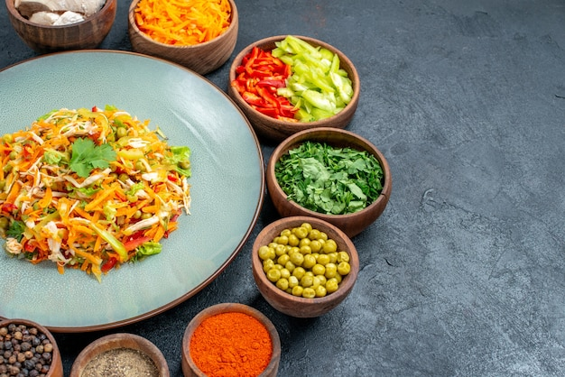 Salada de legumes de frente com legumes frescos na refeição madura de salada de mesa escura