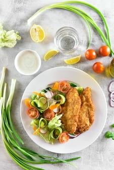 Salada de legumes de tomate, abobrinha, rabanete, verduras e schnitzel