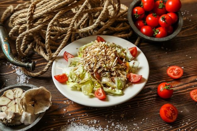 Salada de legumes de vista lateral em um prato com tomate cereja em uma tigela com uma corda em cima da mesa