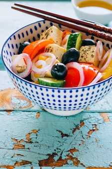 Salada de legumes e azeitonas com pauzinhos no fundo azul de madeira