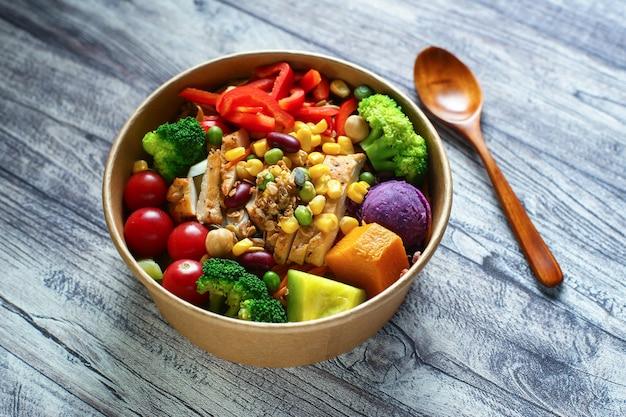 Salada de legumes e frango em uma tigela de papel na mesa de madeira