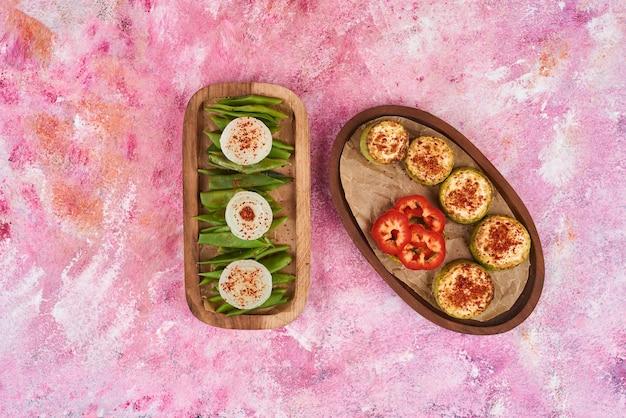 Salada de legumes e frutas em tábuas de madeira.