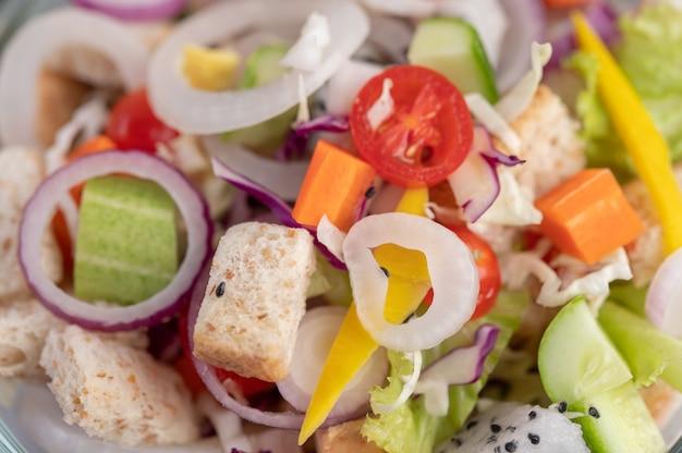 Salada de legumes e frutas em um prato branco.