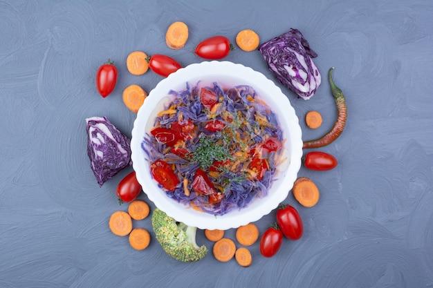Salada de legumes e molho com ingredientes ao redor.