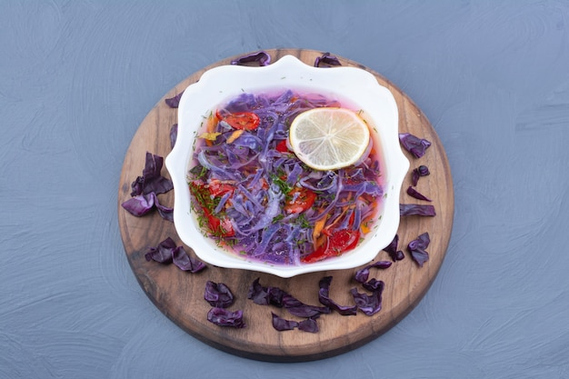 Salada de legumes e molho com repolho roxo em uma tigela de cerâmica branca.