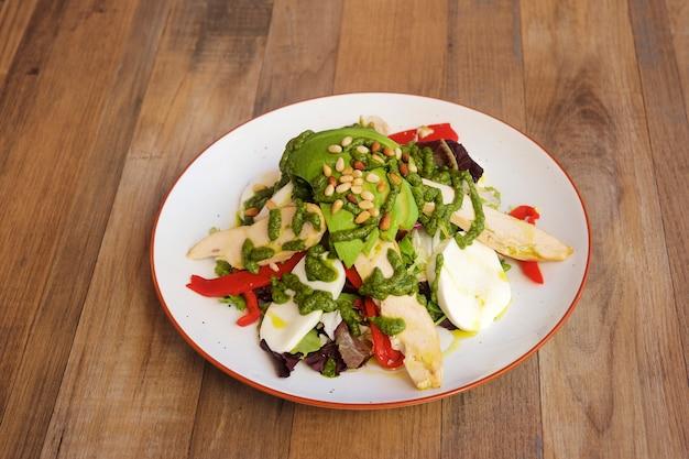 Salada de legumes e peixes em fundo de madeira.