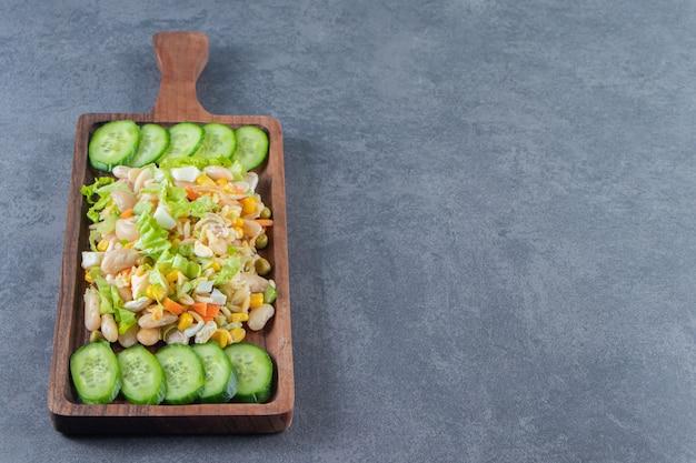 Salada de legumes e pepinos fatiados em uma placa, no fundo de mármore.
