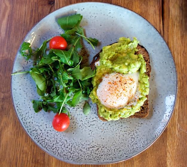Salada de legumes e uma fatia de pão com ovo frito