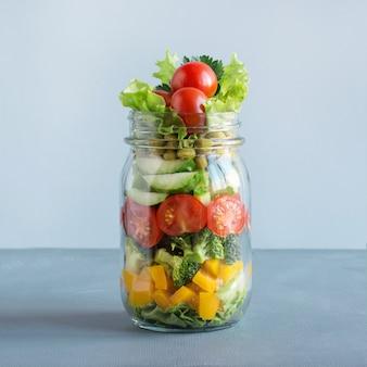 Salada de legumes em frasco de pedreiro para comer no escritório.