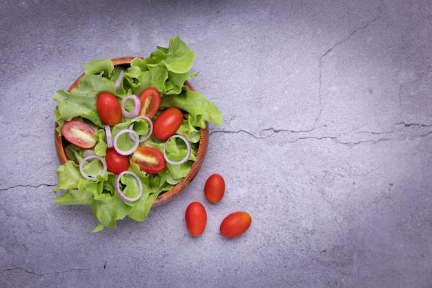Salada de legumes em madeira em cima da mesa na sala da cozinha.