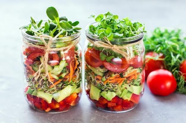 Salada de legumes em potes abertos com tomates na luz de fundo de mármore