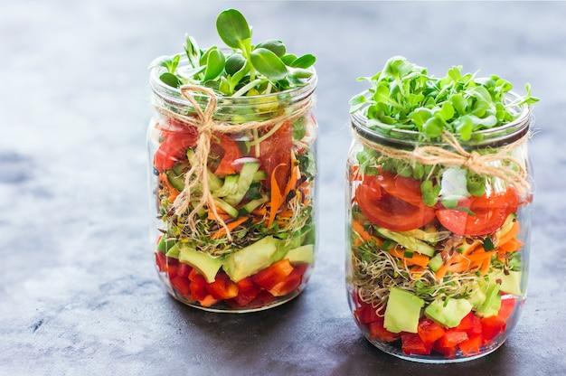 Salada de legumes em potes abertos sobre fundo claro de mármore