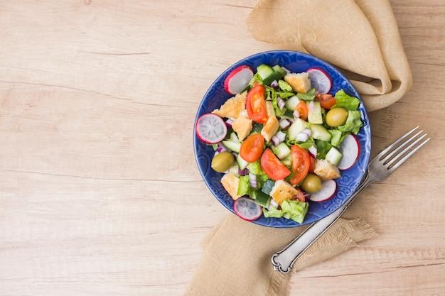 Salada de legumes em tigela na mesa de madeira