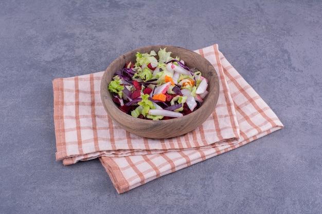 Salada de legumes em travessa de madeira com mistura de ingredientes