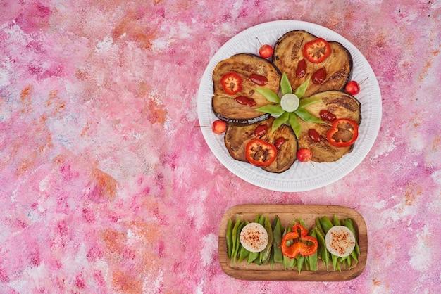 Salada de legumes em travessa de madeira e no prato branco.