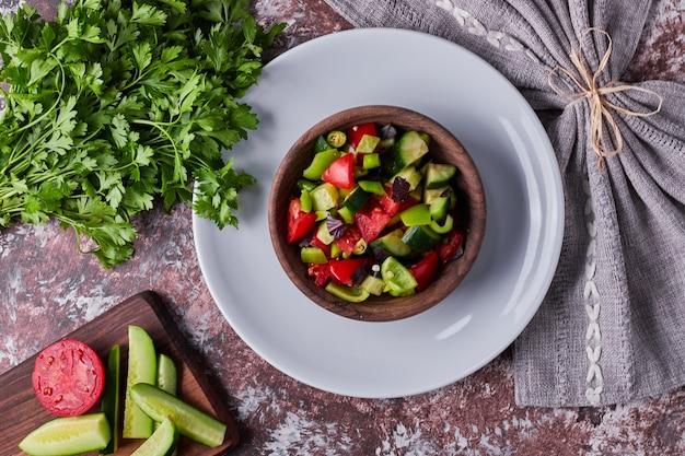 Salada de legumes em um copo de madeira em um prato branco, vista de cima