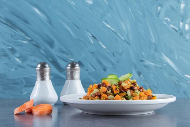 Salada de legumes em um prato ao lado de cenouras fatiadas e sal na superfície de mármore