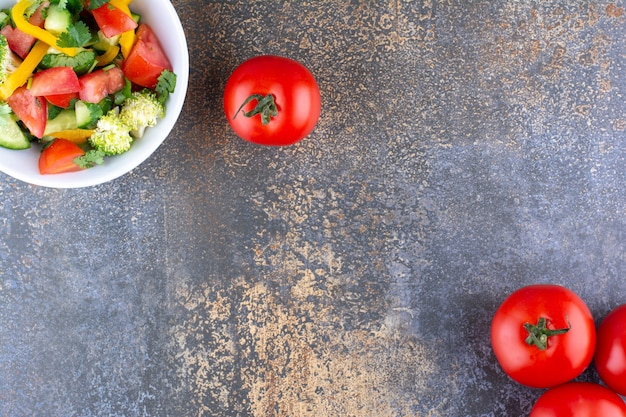 Salada de legumes em um prato branco com tomates vermelhos ao redor