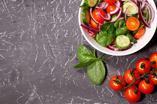 Salada de legumes em um prato branco sobre um fundo cinza, ao lado da pimenta búlgara, tomates