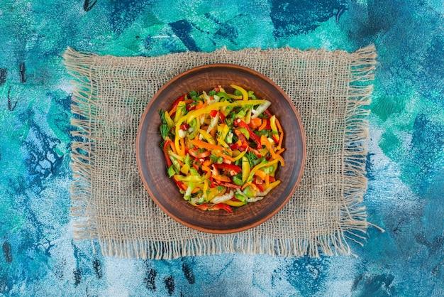 Salada de legumes em um prato na serapilheira, sobre o fundo azul.