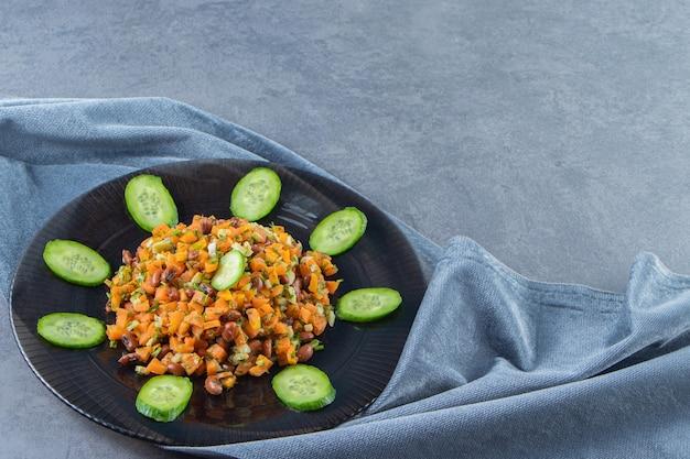 Salada de legumes em um prato sobre uma toalha, na superfície de mármore.