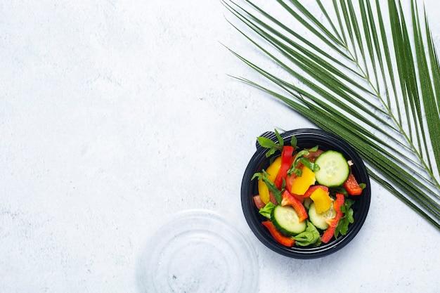 Salada de legumes em uma tigela descartável de plástico e uma folha verde de uma palmeira em um fundo de biton.