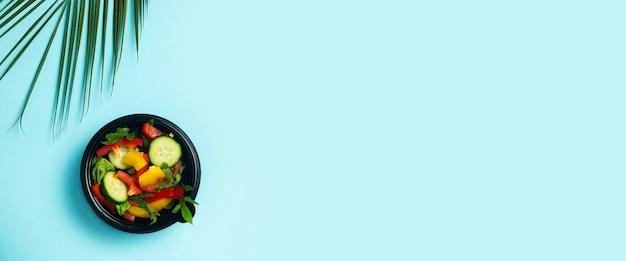 Salada de legumes em uma tigela descartável de plástico e uma folha verde de uma palmeira sobre um fundo azul