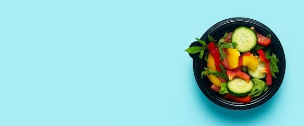 Salada de legumes em uma tigela descartável de plástico sobre um fundo azul claro. vista superior, configuração plana. bandeira.