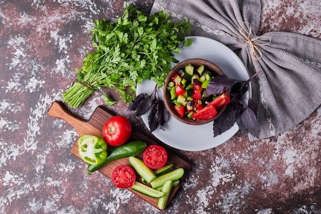Salada de legumes em uma xícara de madeira servida com ervas no mármore.
