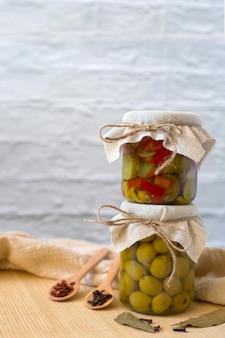 Salada de legumes enlatada em uma jarra em uma jarra com azeitonas em conserva