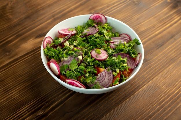 Salada de legumes fresca colorida na superfície de madeira