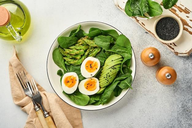 Salada de legumes fresca com abacate, aspargos, ovos amassados, espinafre com sementes de gergelim preto no prato