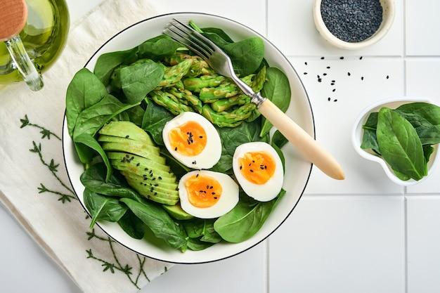 Salada de legumes fresca com abacate, aspargos, ovos cozidos na superfície de azulejos brancos. vista do topo.