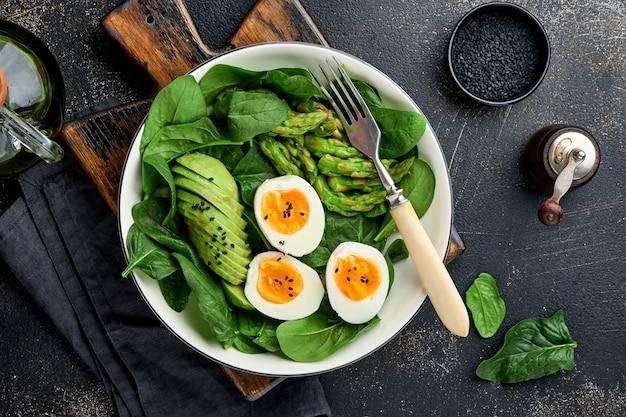 Salada de legumes fresca com abacate, aspargos, ovos cozidos na superfície de concreto escuro. vista do topo.