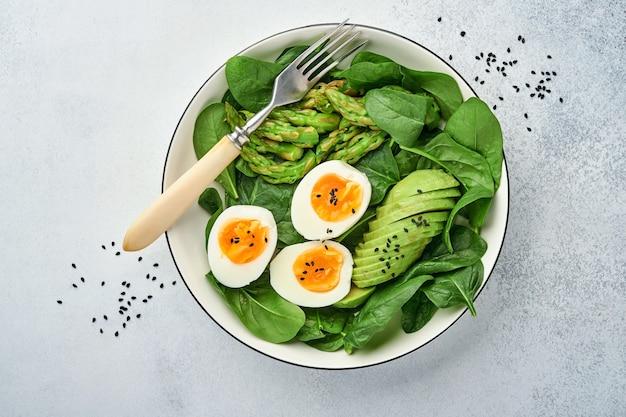 Salada de legumes fresca com abacate, aspargos, ovos cozidos na superfície de concreto leve. vista do topo.