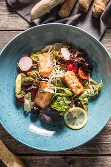 Salada de legumes fresca com azeite de salmão assado e baguete.