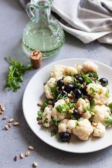 Salada de legumes fresca com couve-flor, azeitonas, salsa e pinhões.
