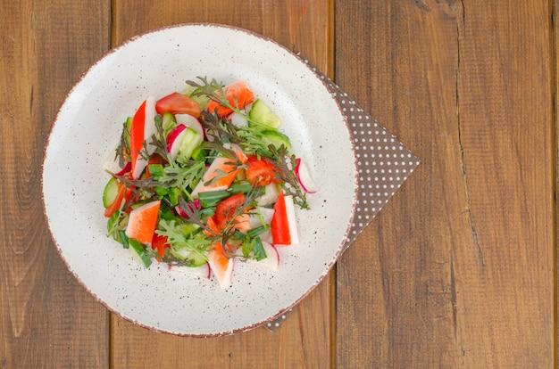 Salada de legumes fresca com palitos de caranguejo.