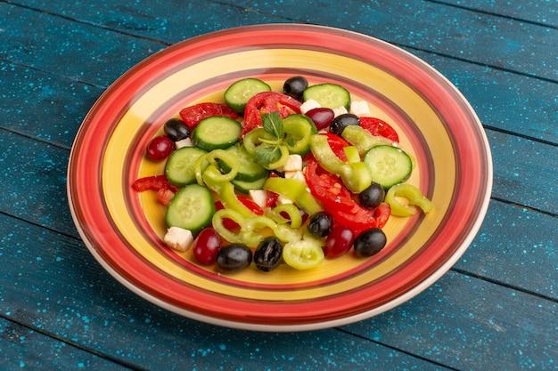 Salada de legumes fresca de vista frontal com pepinos fatiados, tomates, azeite e queijo branco dentro do prato com tomates na superfície azul-escura comida vegetal salada refeição lanche