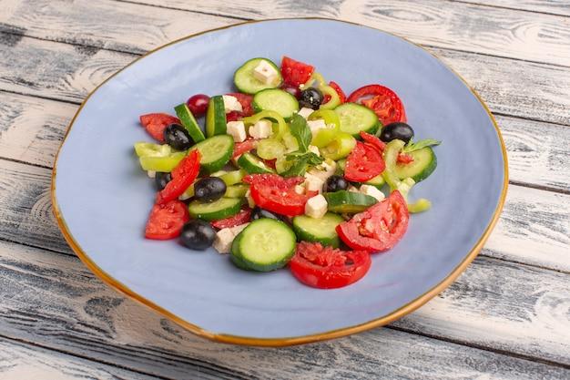 Salada de legumes fresca de vista frontal com pepinos fatiados, tomates, azeitona, dentro do prato, na superfície cinza, cor de refeição de salada de legumes