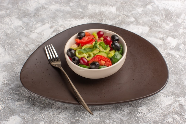 Salada de legumes fresca de vista frontal com pepinos fatiados, tomates, azeitona e queijo branco dentro de um prato marrom na mesa cinza comida de vegetais salada refeição